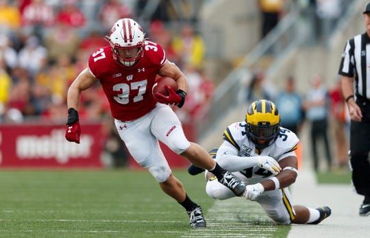 Wisconsin running back Garrett Groshek after catching a pass in front of Michigan linebacker Jordan Anthony (34) during the second quarter at Camp Randall Stadium, Saturday, Sept. 21, 2019, in Madison, Wis.