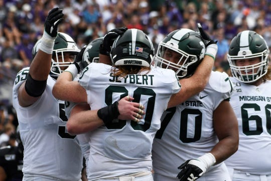 Michigan State tight end Matt Seybert (80) celebrates with offensive tackle Jordan Reid (55) and offensive lineman Tyler Higby (70), after scoring a touchdown against Northwestern during the second half Saturday, Sept. 21, 2019, in Evanston, Ill.