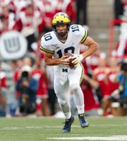 Michigan quarterback Dylan McCaffrey rushes with the ball during the third quarter against Wisconsin, Saturday, Sept. 21, 2019, in Madison, Wis. Wisconsin won 35-14.