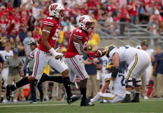 Wisconsin linebacker Chris Orr (54) celebrates a fumble recovery late in the 4th quarter, as Michigan quarterback Shea Patterson (2) is consoled after he fumbled by lineman Jalen Mayfield during the 2nd half Saturday, Sept. 21, 2019, in Madison, Wis. Wisconsin won 35-14.