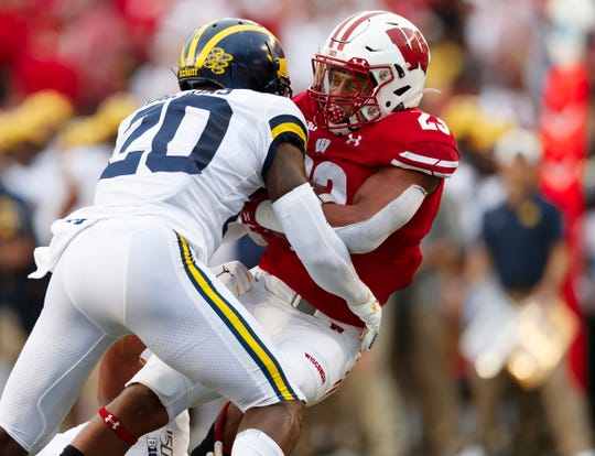 Wisconsin Badgers running back Jonathan Taylor is tackled by Michigan Wolverines defensive back Brad Hawkins during the first quarter at Camp Randall Stadium, Sept. 21, 2019 in Madison, Wis.