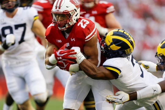 Wisconsin's Jonathan Taylor runs against Michigan's Khaleke Hudson during the first half Sept. 21, 2019.