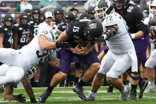 Michigan State linebacker Joe Bachie (35) and defensive tackle Mike Panasiuk (72) sack Northwestern quarterback Hunter Johnson during the first half Saturday, Sept. 21, 2019, in Evanston, Ill.