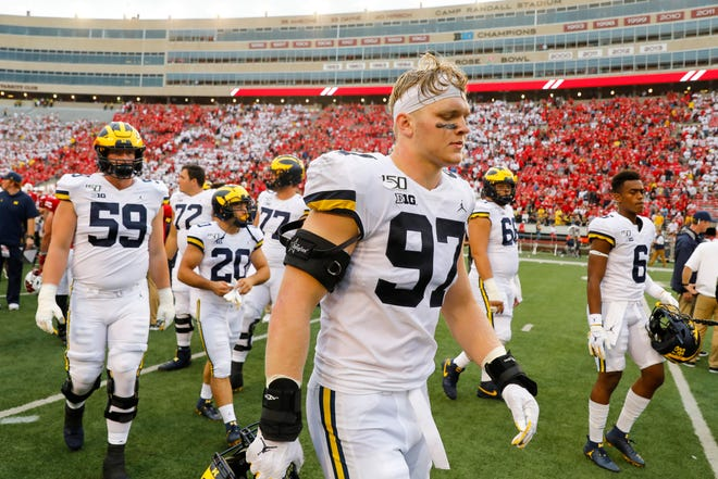 Michigan defensive lineman Aidan Hutchinson walks off the field with teammates, after losing 35-14 to Wisconsin, Saturday, Sept. 21, 2019, in Madison, Wis.