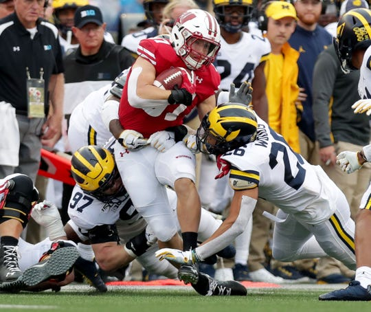 Wisconsin's Garrett Groshek is tackled by Michigan's J'Marick Woods, right, and Aidan Hutchinson, left, after a catch during the first half, Saturday, Sept. 21, 2019, in Madison, Wis. Wisconsin won 35-14.