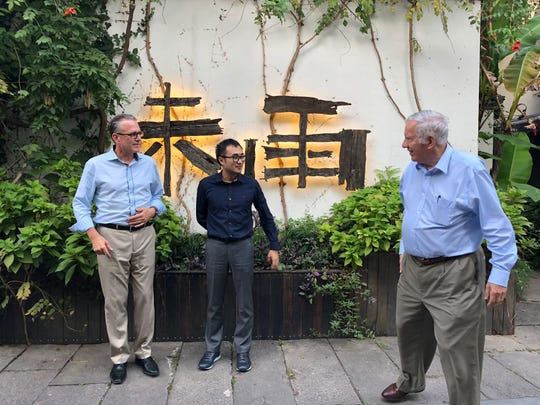 Mike Wang , CEO of Madison Heights-based Quadrobot, center, with  Joe Buick, left, and John Manoogian -- both Quadrobot board members-- in China on Oct. 1, 2018.  They are marketing their Quadrobot U1 package delivery vehicle to China.