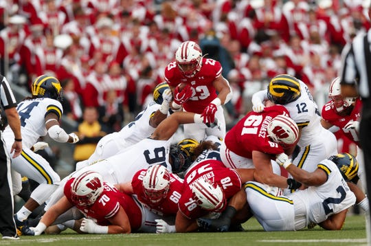 Wisconsin Badgers running back Jonathan Taylor leaps for a first down during the first quarter against the Michigan Wolverines at Camp Randall Stadium, Sept. 21, 2019.