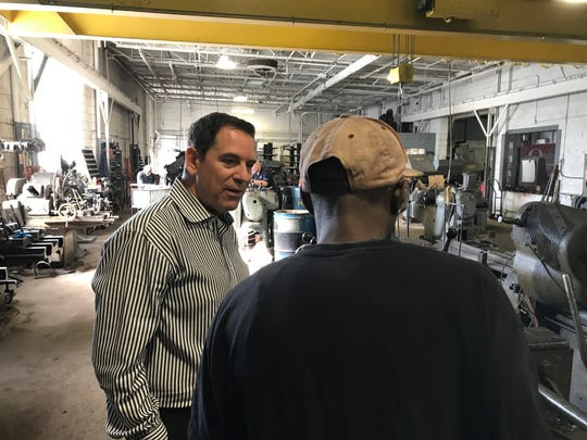 Matthew Seely, owner of a metal fabricating firm in Detroit, talks to one of his 10 employees on Sept. 19, 2019.