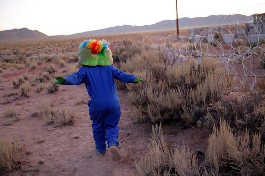 "Martin Custodio pretends to ""Naruto run"" at an entrance to the Nevada Test and Training Range near Area 51 Friday, near Rachel, Nev."
