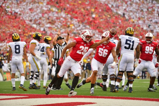 Wisconsin's Eric Burrell holds the football after Michigan's Ben Mason fumbles in the first quarter.