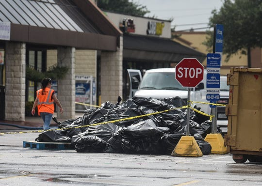 Bags of trash sit in front of the Kroger store, Friday, Sept. 20, 2019 in Beaumont, Texas. East of Houston in Jefferson County, which got hit by more than 40 inches of rain, officials also began taking stock of their damage.
