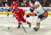 Red Wings forward Taro Hirose (67) challenges a pass from Islanders defenseman Luca Sbisa (21) in the second period.