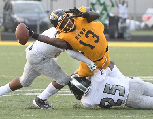 Detroit King's Rashawn Williams refuses to give up, stretching out after a reception with Detroit Cass Tech defenders all over him in the fourth quarter on Friday.