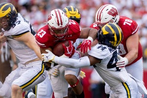 Wisconsin running back Jonathan Taylor pushes past Michigan linebacker Cameron McGrone in the third quarter.