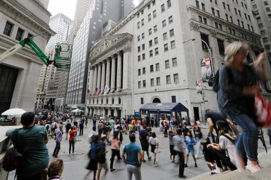 FILE - In this Aug. 23, 2019, file photo pedestrians pass the New York Stock Exchange in New York. The U.S. stock market opens at 9:30 a.m. EDT on Friday, Sept. 6.