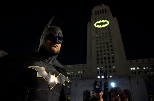 "Tony Bradshaw, of Los Angeles, dressed as Batman, poses in front of a Bat-Signal projected onto City Hall during a tribute to ""Batman"" star Adam West in Los Angeles in 2017."