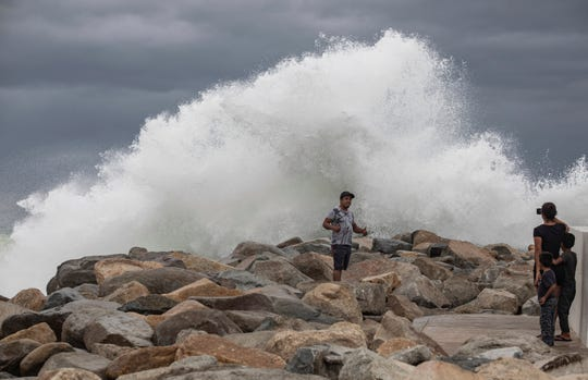 A tourist poses for a photo in front breaking waves before the expected arrival of Hurricane Lorena, in Los Cabos, Mexico on Friday.