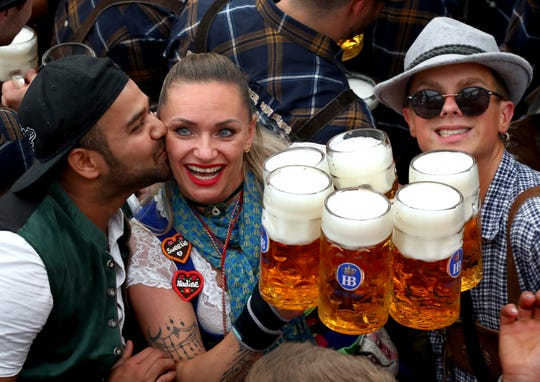 A waitress is kissed by a guest as she holds glasses of beer during the opening of the 186th 'Oktoberfest' beer festival in Munichon  Saturday.