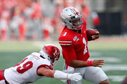 Ohio State quarterback Justin Fields, right, cuts upfield on his way to a touchdown against Miami (Ohio) defensive back Bart Baratti.