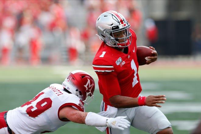 Ohio State quarterback Justin Fields, right, cuts upfield on his way to a touchdown against Miami (Ohio) defensive back Bart Baratti.