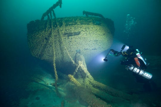 Diver John Scoles maneuvers around the wreckage of the schooners Peshtigo and St. Andrews, lost in 1878 near Beaver Island in northern Lake Michigan on Aug. 24, 2019.