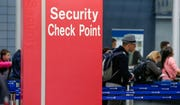 Passengers check into their flights near a security checkpoint sign at O'Hare International Airport in Chicago.