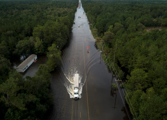 A truck drives through a flooded highway as flooding from the remnants of Tropical Storm Imelda continues in Southeast Texas on Friday, Sept. 20, 2019, in Mauriceville, Texas.