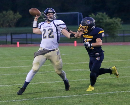 Elmira Notre Dame quarterback Erik Charnetski throws a touchdown pass as Trumansburg's Bryce Grove pressures him during the Crusaders' 30-12 victory Sept. 20, 2019 at Trumansburg.