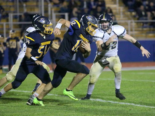 Trumansburg quarterback William Lovejoy carries the ball as Erik Charnetski (22)  of Elmira Notre Dame tries for the tackle and Noah Potenza (54) blocks Sept. 20, 2019 at Trumansburg.
