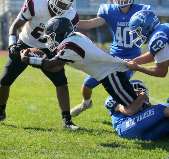 Michael Brown of Elmira stretches with the ball as Horseheads' Hayden Barnes (52) and Austin Cleary (81) make the tackle Sept. 21, 2019 at Horseheads High School.
