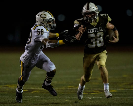 Central's Brennan Schutte (38) runs past Castle defenseman Nyles Sutton (58) at Central Stadium in Evansville, Ind., Friday night, Sept. 20, 2019. The Bears defeated the Castle Knights, 38-7.