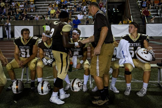 Central's Teorien Evans (2), center left, and Central Head Coach Sean Coultis, center right, shake hands as their team waits for the remaining minute to run off the game clock before celebrating their 38-7 victory over the Castle Knights at Central Stadium in Evansville, Ind., Friday, Sept. 20, 2019.