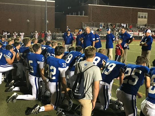 Memorial football head coach John Hurley speaks with his team following Friday's 24-14 victory over Bosse.