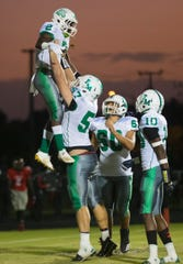 Fort Myers High School's Yasias Young, top, celebrates scoring a touchdown against South Fort Myers with teammates Cayden Baker (57), David Gomez (60) and Joriell Washington (10) on Friday at South. Fort Myers beat South 35-16.