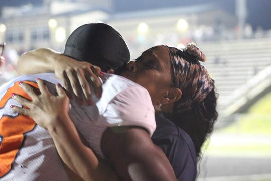 Carolina quarterback Kaleb Whiteside hugs his mother after the Trojans 16-7 win over Liberty Friday night