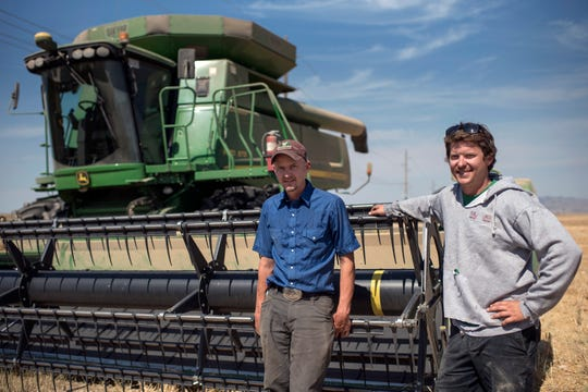 In this Sept. 5, 2019 photo, Mark and Kenny Van Dyke pose for a photo with their combine during harvest near Three Forks, Mont. Looking from a bird's-eye view, Bozeman's history as a farm town can still be seen in certain pockets of wide, open spaces around the city. The brothers are fourth-generation farmers and have worked the land in the Bozeman area all their lives. Growing up, the two helped with the family farming and ranching business. (Rachel Leathe/Bozeman Daily Chronicle via AP)