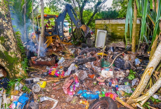 Department of Public Works employee, John Kakas, operates a backhoe in an attempt to sort through old tires, building material and trash stockpiled on the side of a family's home, along Swamp Road in Dededo, on Saturday, Sept. 21, 2019. Health officials, government agencies and Dededo mayor office staff, continue with efforts to eliminate possible breeding containers for the mosquitoes population in the area after a man living in the area as the second person on island to have locally acquired the dengue fever virus.
