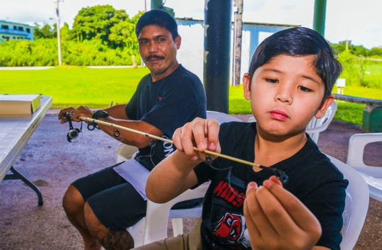 Jose Camacho, 9, cafefully threads mono-filament line through the eyelets of his fishing pole as he and his father, Joey Camacho, attend a fishing clinic held by the Guam Department of Agriculture's Division of Aquatic and Wildlife Resources at the Mangilao softball field on Saturday, Sept. 21, 2019. The clinic was being held by the agency, to teach young anglers basic rod and reel fishing skills, in preparation for the annual Kids' Fishing Derby scheduled for Saturday, September 28.