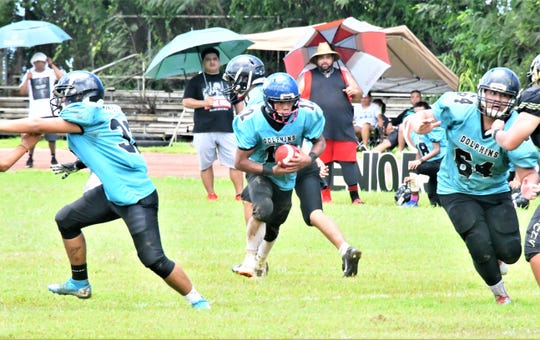 Southern High School running back Conan Baza looks for an opening against the Tiyan High School defense during their IIAAG High School Football game Sept. 21 at Southern High School. The Dolphins beat the Titans 20-16.