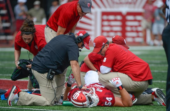 Indiana Hoosiers Tom Allen and the medical staff check on offensive lineman Coy Cronk (54) during the game against UConn at Memorial Stadium in Bloomington, Ind., on Saturday, Sept. 21, 2019.