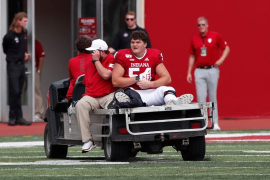 Indiana Hoosiers offensive lineman Coy Cronk (54) is carted off the field with a leg injury in a game against the Connecticut Huskies during the first quarter at Memorial Stadium .