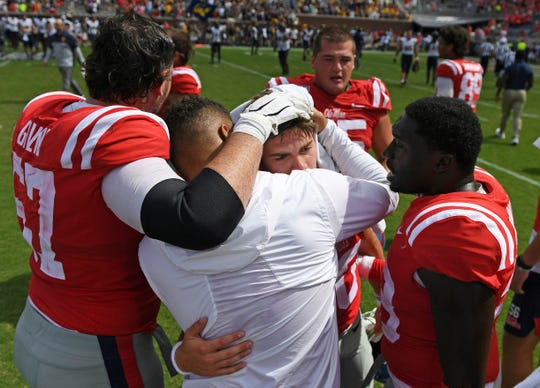 Ole Miss players console quarterback John Rhys Plumlee, center, after an NCAA college football game against California in Oxford, Mississippi, on Saturday, Sept. 21, 2019. California won 28-20.