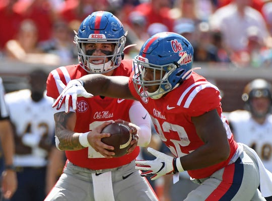 Ole Miss Matt Corral (2) hands the ball off to running back Scottie Phillips (22) against California in Oxford, Miss., Saturday, Sept. 21, 2019.