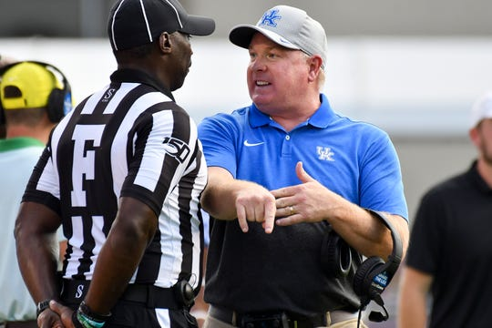 Sep 21, 2019; Starkville, MS, USA; Kentucky Wildcats head coach Mark Stoops speaks with field judge Wes Booker as a play is reviewed during the second quarter of the game against the Mississippi State Bulldogs at Davis Wade Stadium. Mandatory Credit: Matt Bush-USA TODAY Sports
