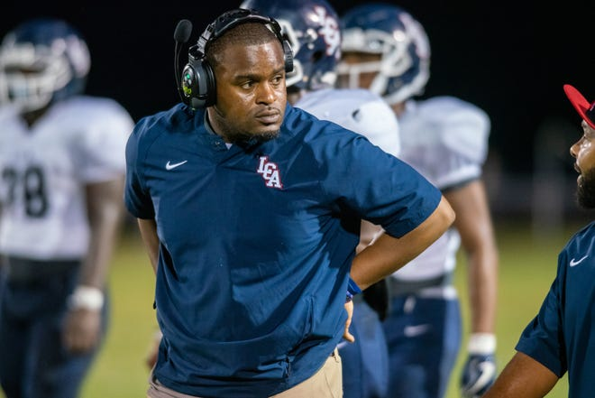 LCA head coach Jacarde Carter listens to his assissting coaches on the sideline as the Acadiana High Wreckin' Rams take on the Lafayette Christian Academy Knights Friday, Sept. 20, 2019.