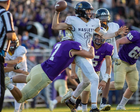 Fowlerville's Nathan Ash grabs hold of Haslett quarterback Xander Thelen on Friday, Sept. 20, 2019.