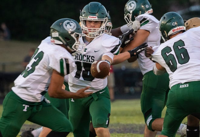 Trinity quarterback Nathan McElroy hands the ball off to running back Armon Tucker in the first half Friday, Sept. 20, 2019 in Louisville Ky. Male goes on to win in double overtime 20-17.
