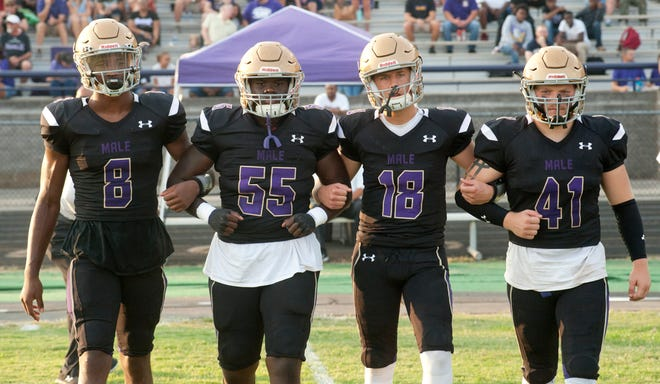 Male co-captains (l-r) Male wide receiver Izayah Cummings, Male defensive end-linebacker Chaz Webster, Male quarterback Elijah Parish and Male running back Joe Kuerzi walk out to mid-field for the coin toss. 20 September 2019