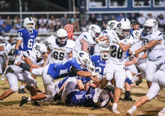 Providence's Colin Flake scrambles for yardage as Charlestown's defense tried to stop him late in the second half. The Pirates defeated the Pioneers 13-7 Friday night.