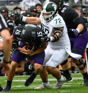 Sep 21, 2019; Evanston, IL, USA; Michigan State Spartans defensive tackle Mike Panasiuk (72) sacks Northwestern Wildcats quarterback Hunter Johnson (15) during the first half at Ryan Field. Mandatory Credit: Matt Marton-USA TODAY Sports